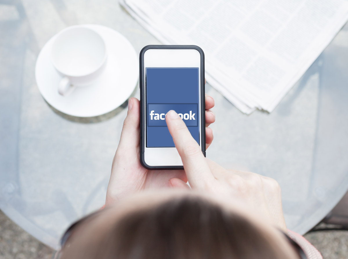 Woman Pressing the Facebook Logo on Smartphone