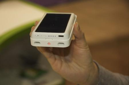 Eton's solar-powered case/battery for iPhone (solar-side up). The red light means it's generating power.