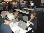 Apple's Patty Metason, right, signs in an attendee to see an upcoming demo