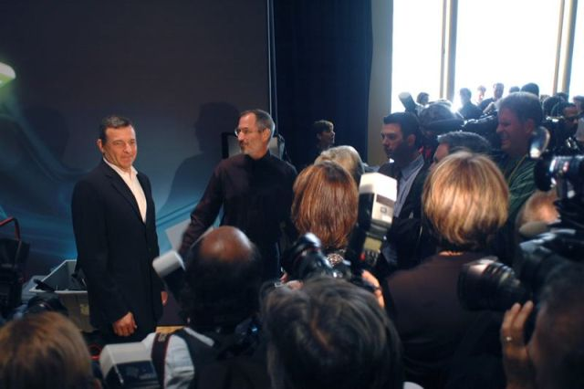 Disney CEO Bob Iger and Apple CEO Steve Jobs being mobbed by reporters.