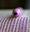 Photo of a purple highlighter resting on a marked-up page in a book.
