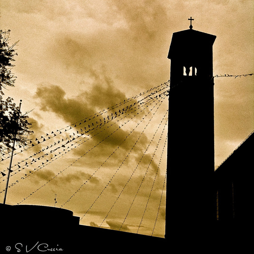 A silhouette of a church bell tower
