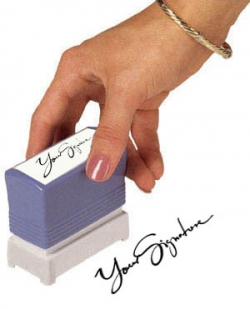 A woman's hand stamping her signature onto paper with a traditional rubber stamp.