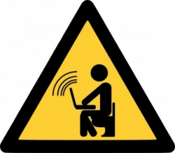 A yellow traffic warning sign depicting a stick-man sitting with a laptop transmitting a Wi-Fi signal.