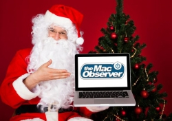 Santa Clause holding up a laptop