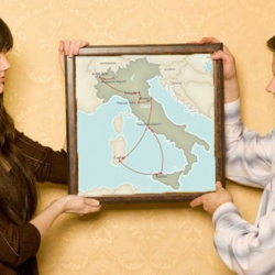 A young couple holding up a framed travel itinerary map
