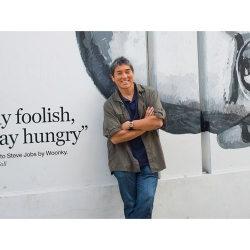 Guy Kawasaki standing in front of mural of Steve Jobs