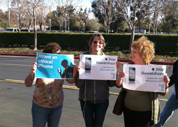 Protestors hold signs outside Apple shareholder meeting