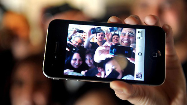 Picture of an iPhone showing an image of happy people using their iPhone cameras.