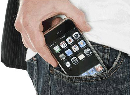 A hand slipping an iPhone into a jeans pocket.