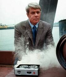 A scene from the original episodes of Mission Impossible where an agent is standing next to a tape recorder self-destroying.