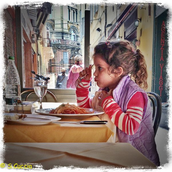 An iPhone image of a girl eating spaghetti