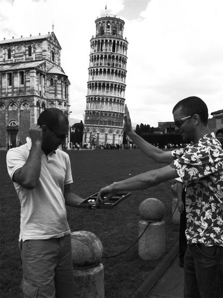 Two men playing a board game next to the Leaning Tower of Pisa