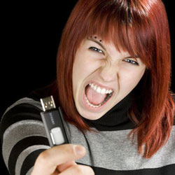 A screaming red-headed young lady holding up a thumb drive