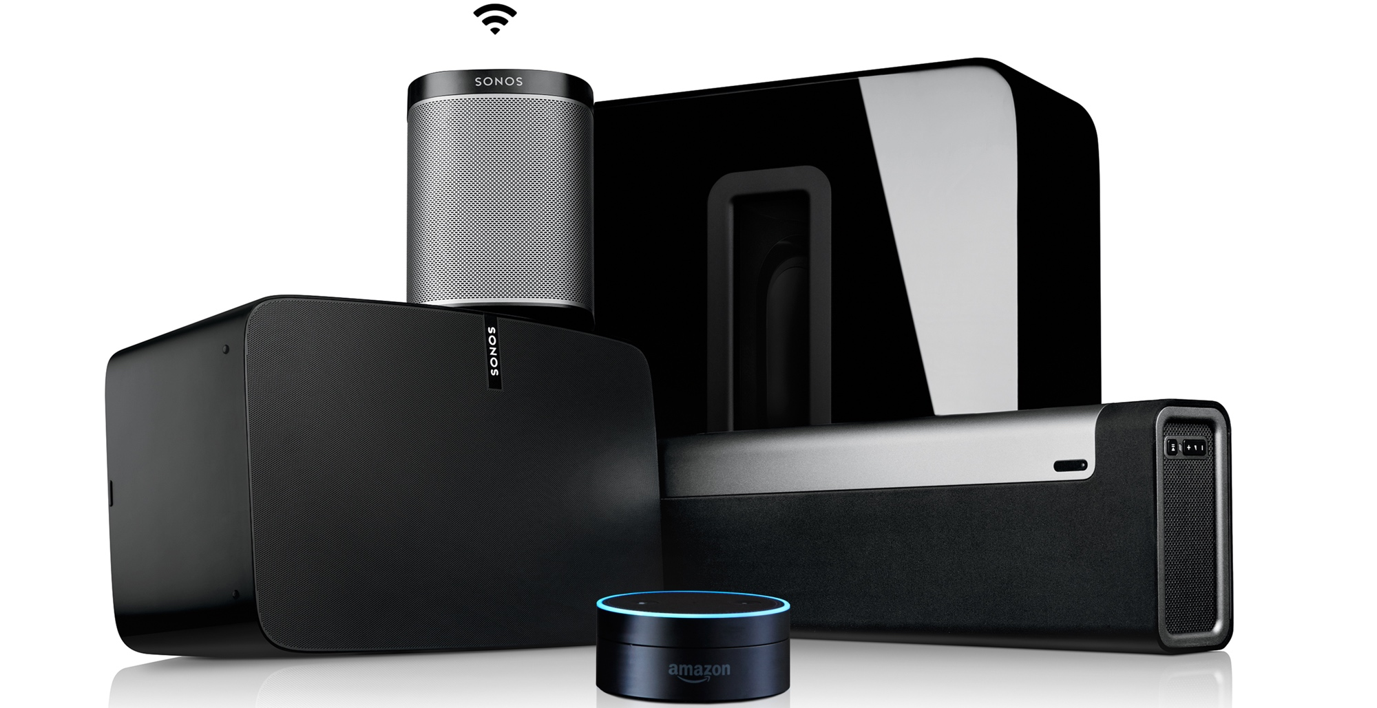 pile of sonos speakers with Amazon Alexa Dot front and center