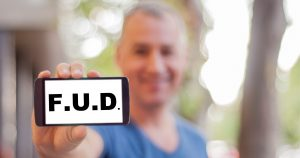 """man holding iPhone that says """"F.U.D."""" on it."""