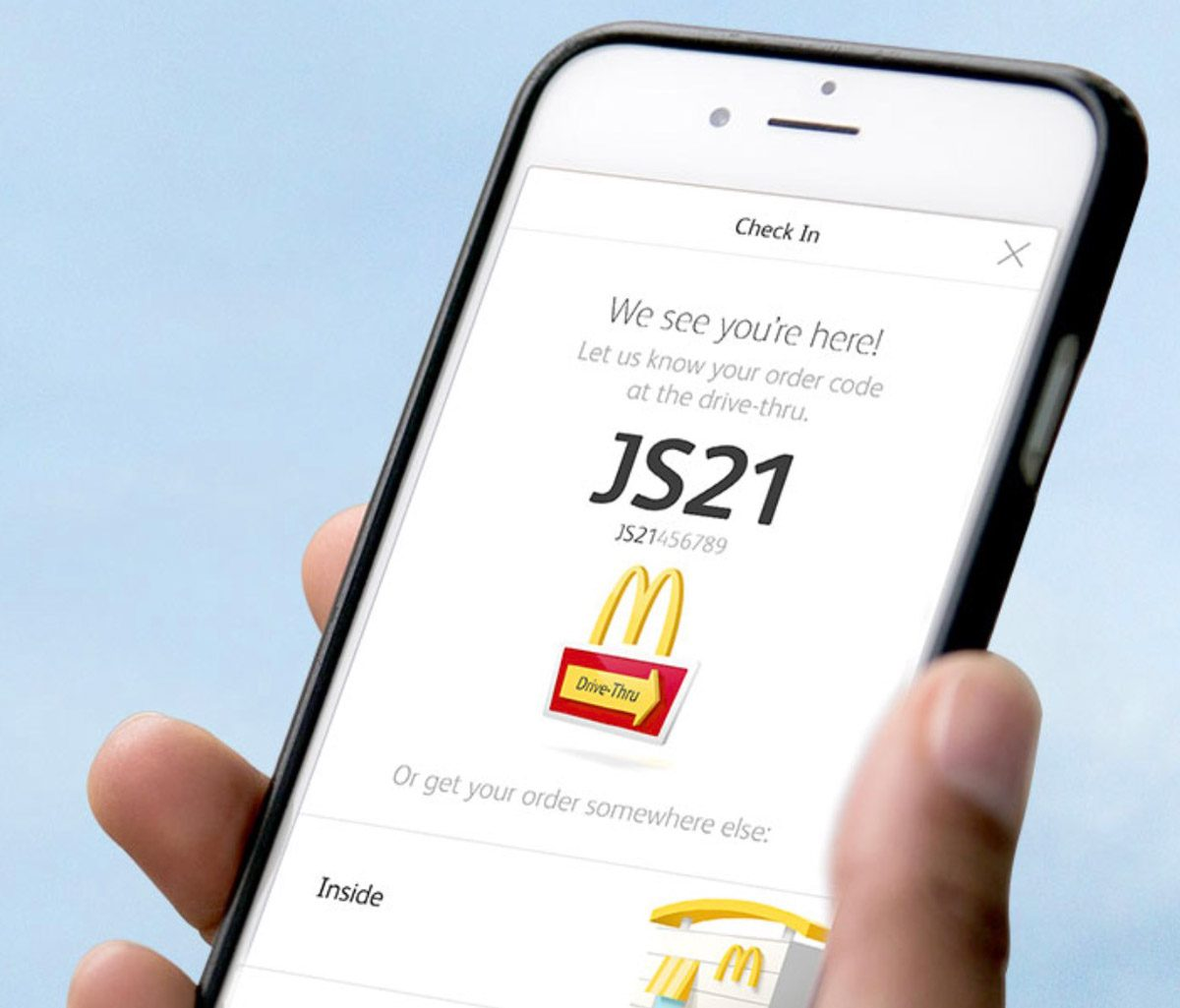 Someone holding an iPhone with McDonald's Mobile Ordering app