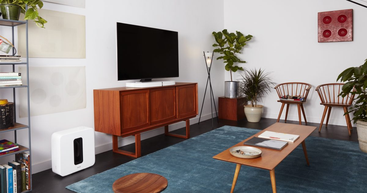 White Sonos PLAYBASE on a TV stand underneath TV in the living room