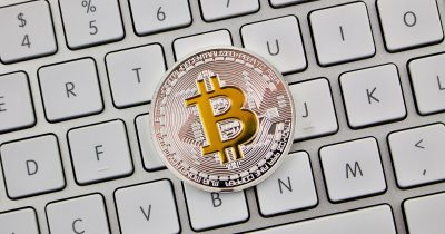 A physical Bitcoin on a keyboard