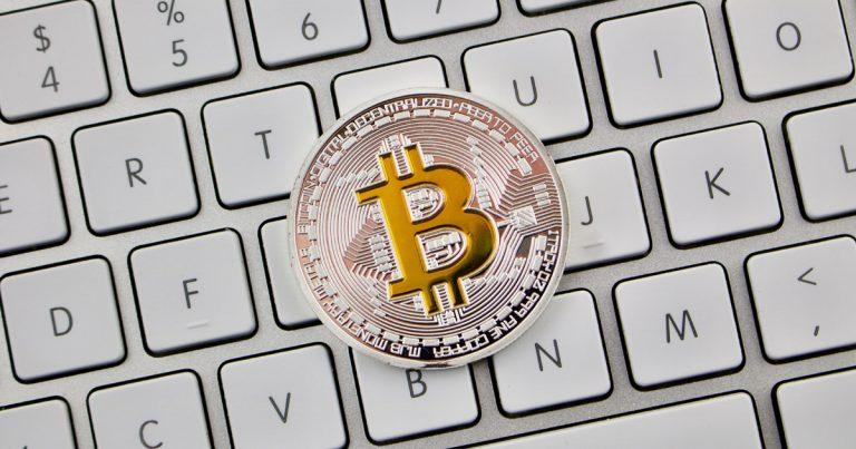 A physical Bitcoin on a keyboard