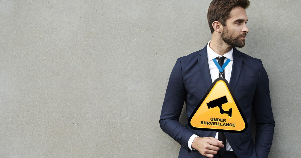 """A well-dressed man wearing a warning sign that says """"Under Surveillance"""""""