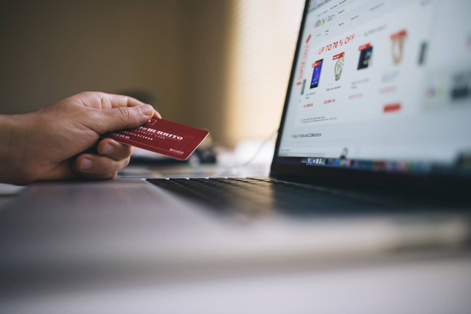 Stock image of consumer using credit card at computer. To find the TransUnion credit freeze page, follow these steps.