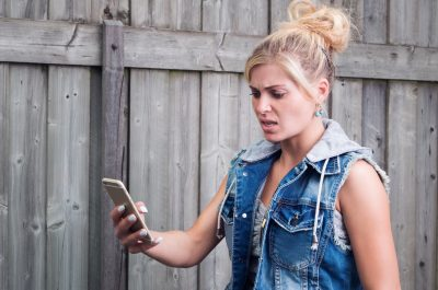 Frustrated woman looking at iPhone