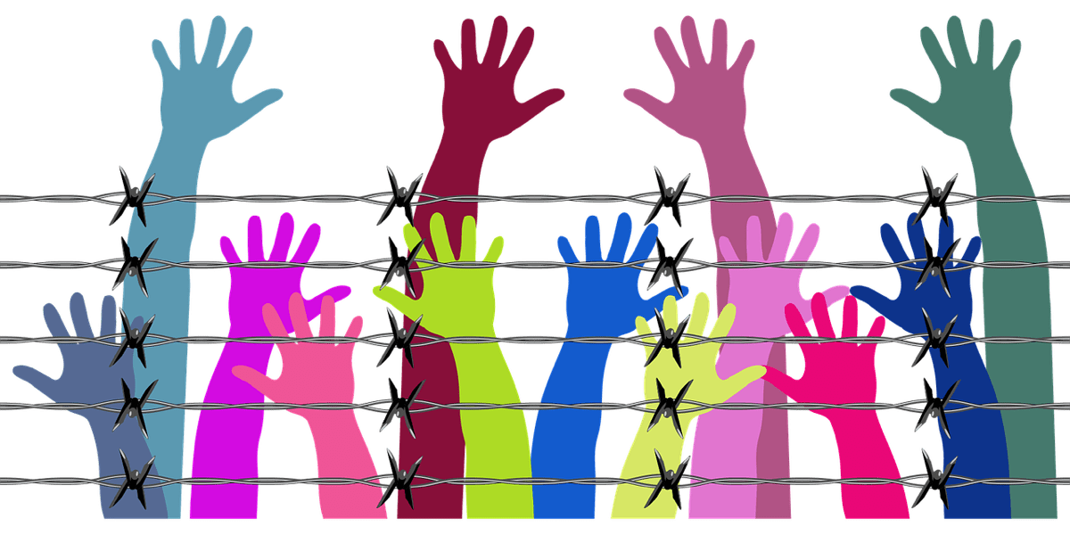 Image of hands reaching over barbed wire jail. Public utility app Appolition aims to raise funds for bail.