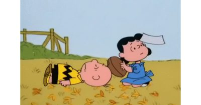 Lucy holds the football for Charlie Brown, yet again