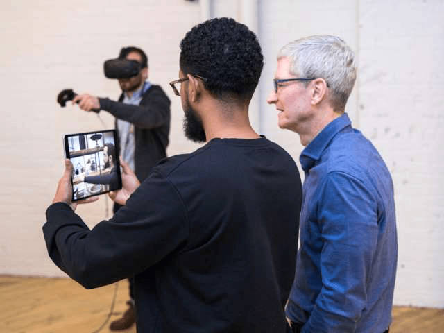 Tim Cook watching an AR shopping experience at Shopify.