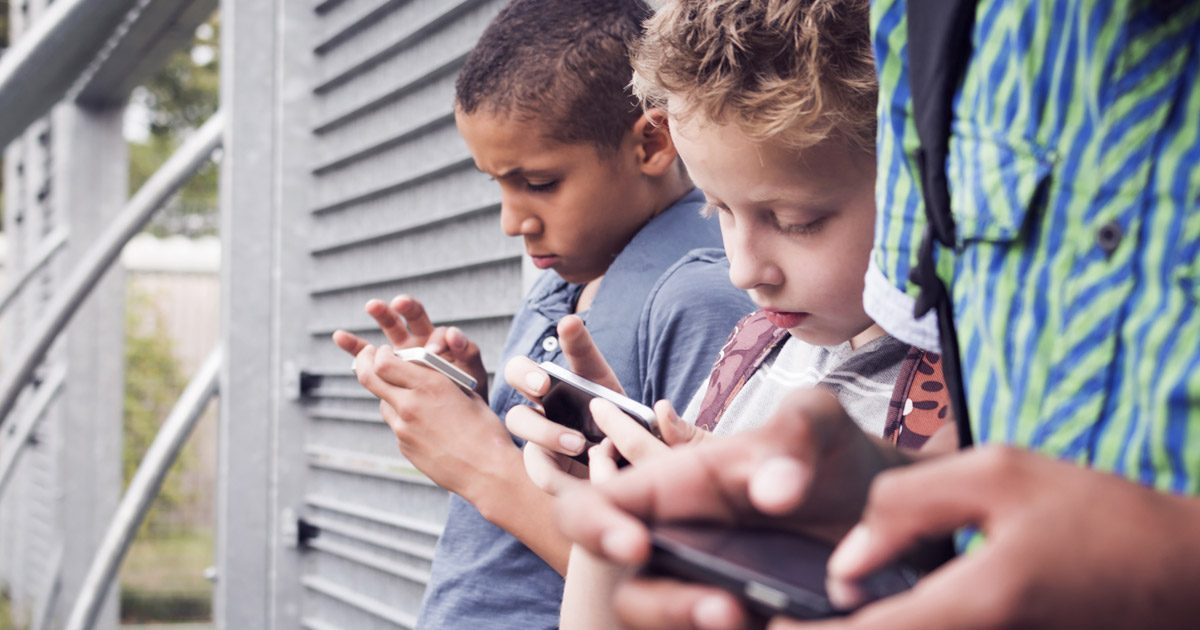 Kids lining up against the wall with smartphones
