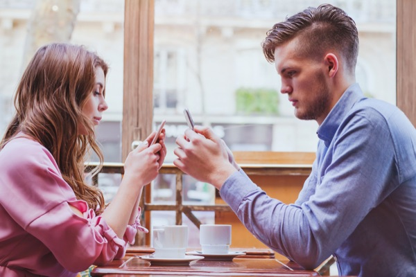 Dating couple with smartphones. Consulting Artificial Intelligence