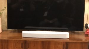 Sonos Beam soundbar in front of dark TV