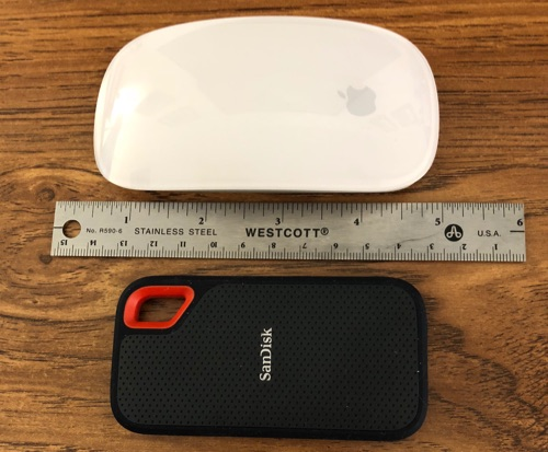SanDisk Extreme Portable SSD next to ruler and Magic Mouse.