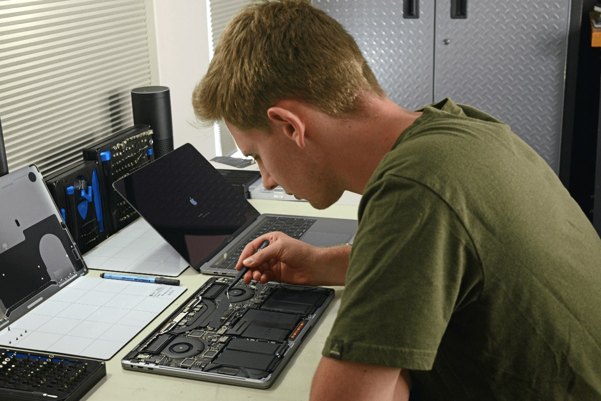 image of ifixit technician fixing a macbook pro.