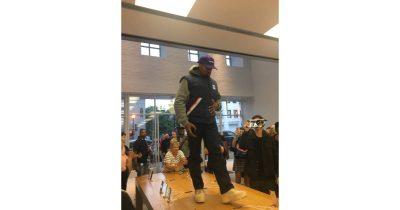 Kanye West walking on iPhone display table in Georgetown Apple Store
