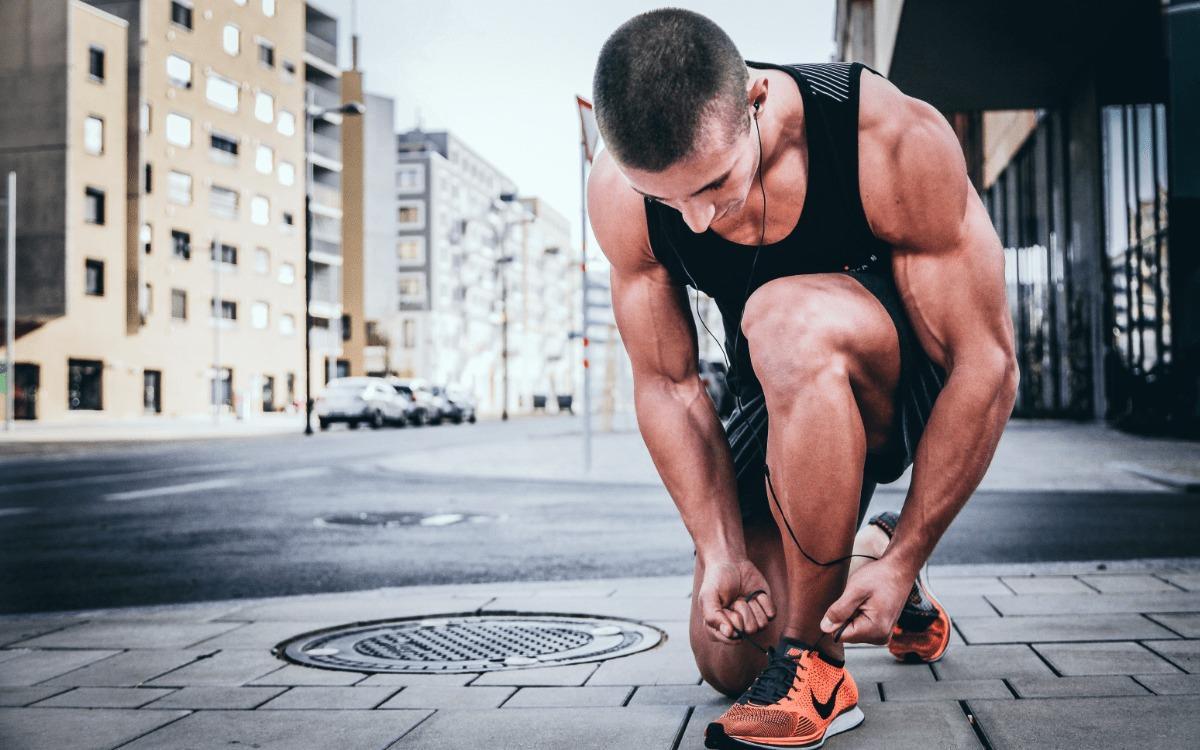 man tying shoes during a run