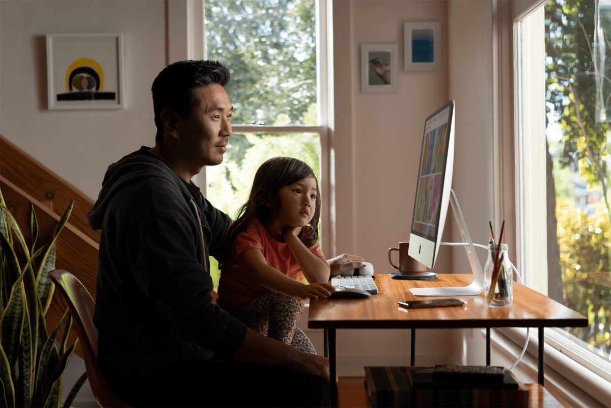 father and daughter using an imac