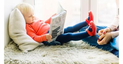 Kid reading a paper book.