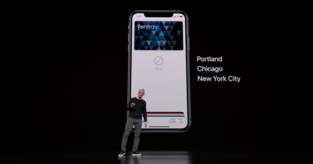 Tim Cook on stage in front of a slide displaying an iPhone with a transit card in the Wallet app