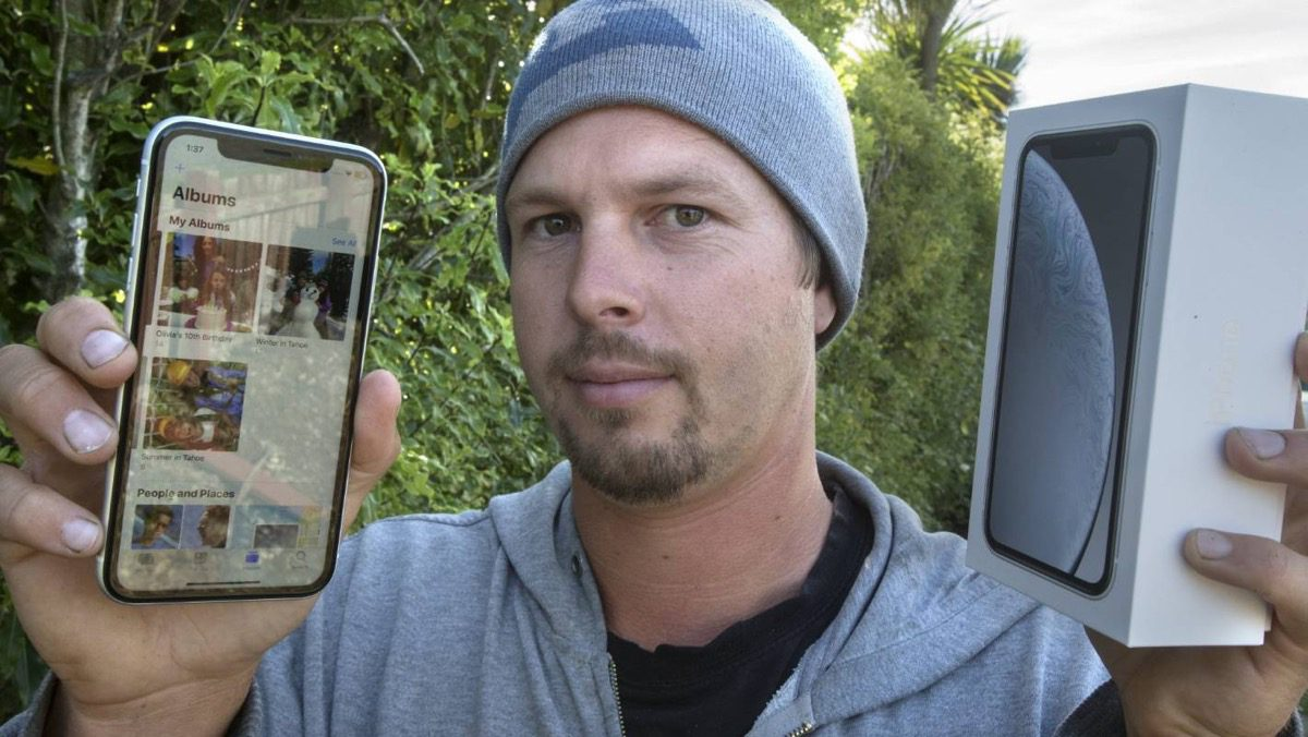 Image of man holding previously used iphone