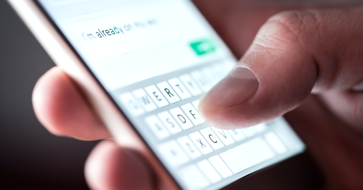 Person using an iPhone to text.
