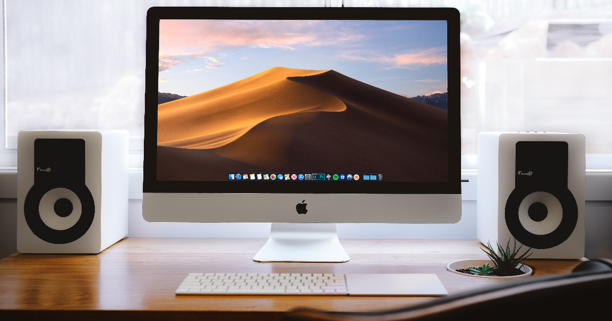 An iMac on a desk with two speakers.