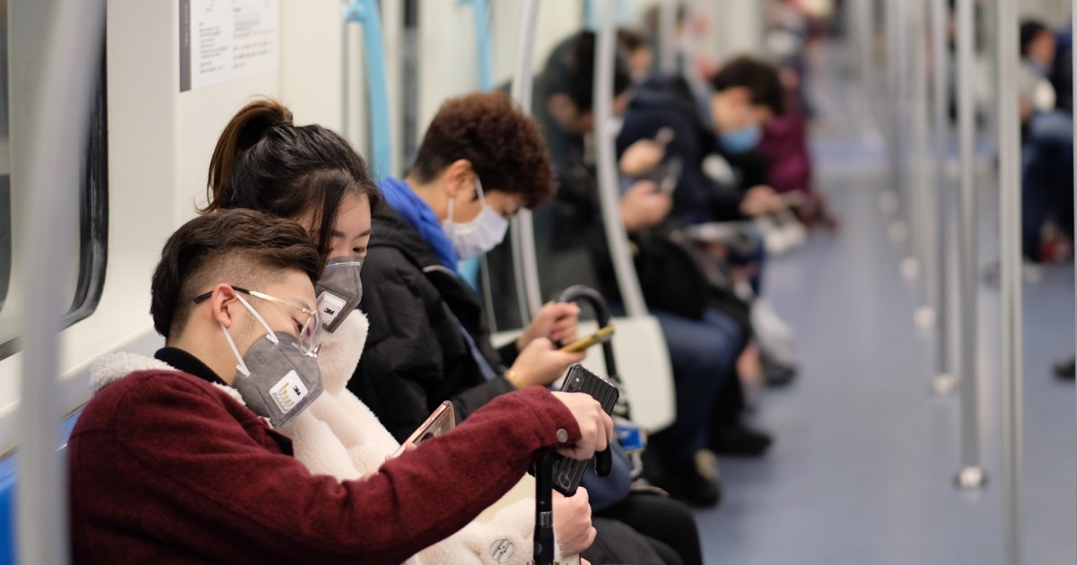 People wearing masks and using their smartphones.