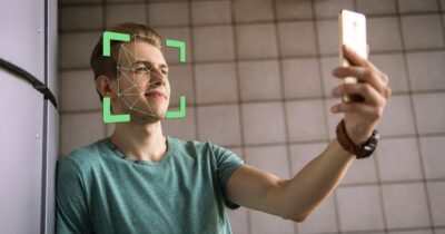 Image of man holding phone to his face to demonstrate facial recognition