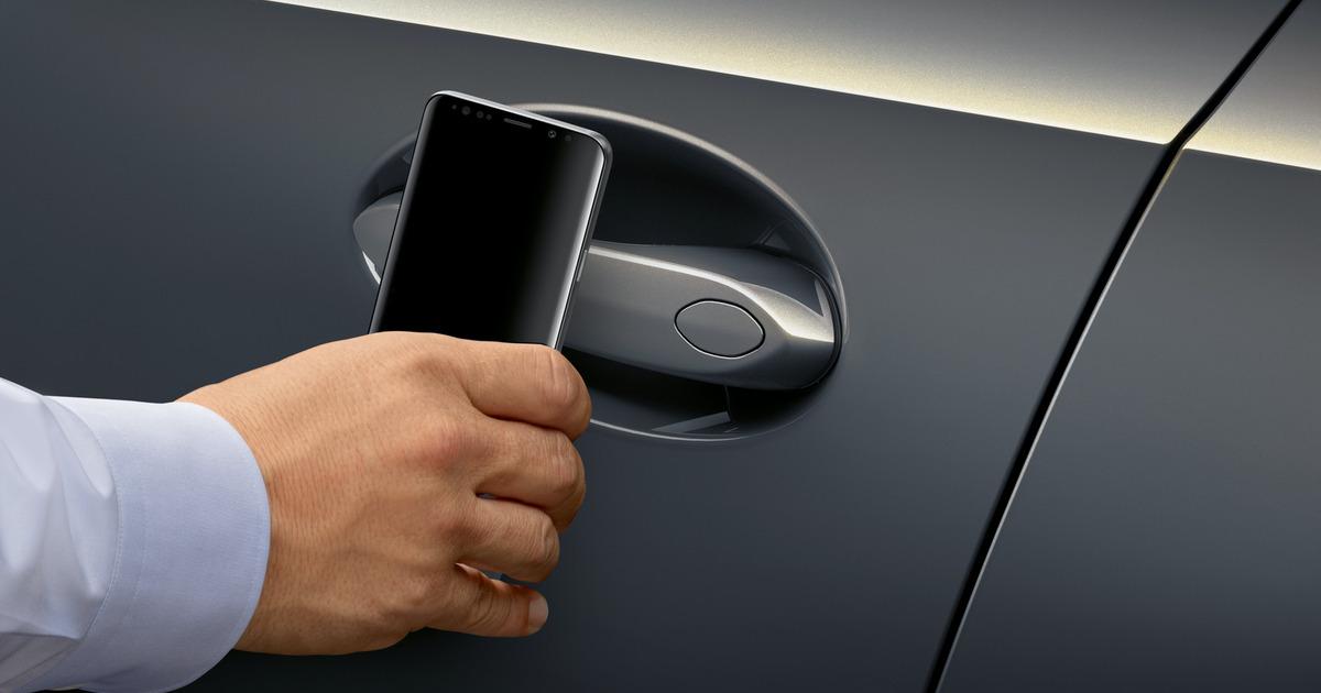 Hand using 'CarKey' with a BMW