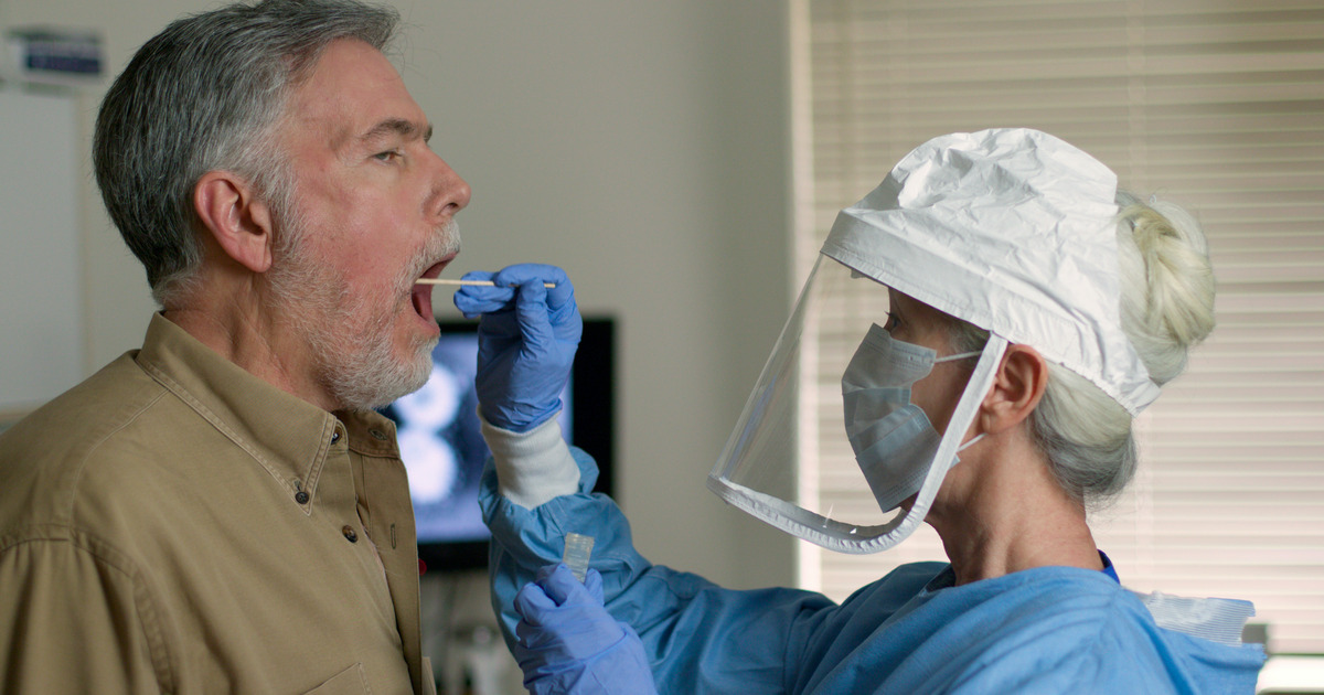 Nurse testing patient for COVID-19 Wearing Face Shield