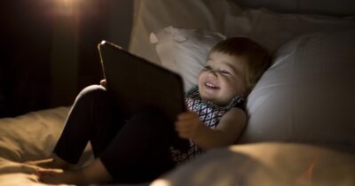 Toddler using an iPad laying on a bed.
