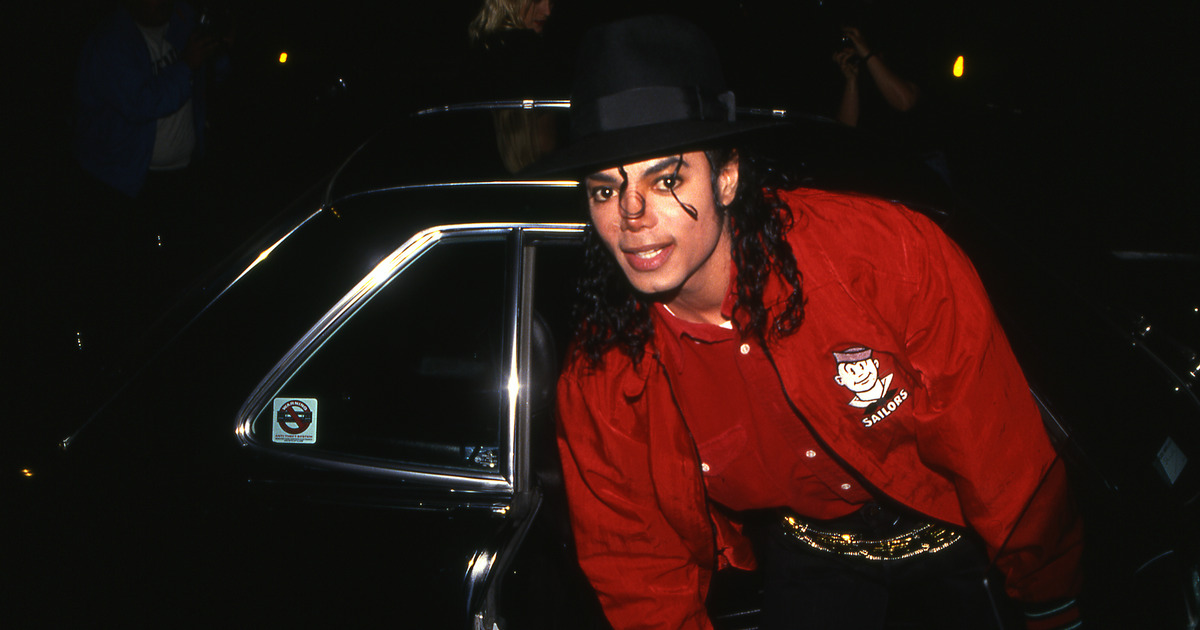 Michael Jackson in front of a black car