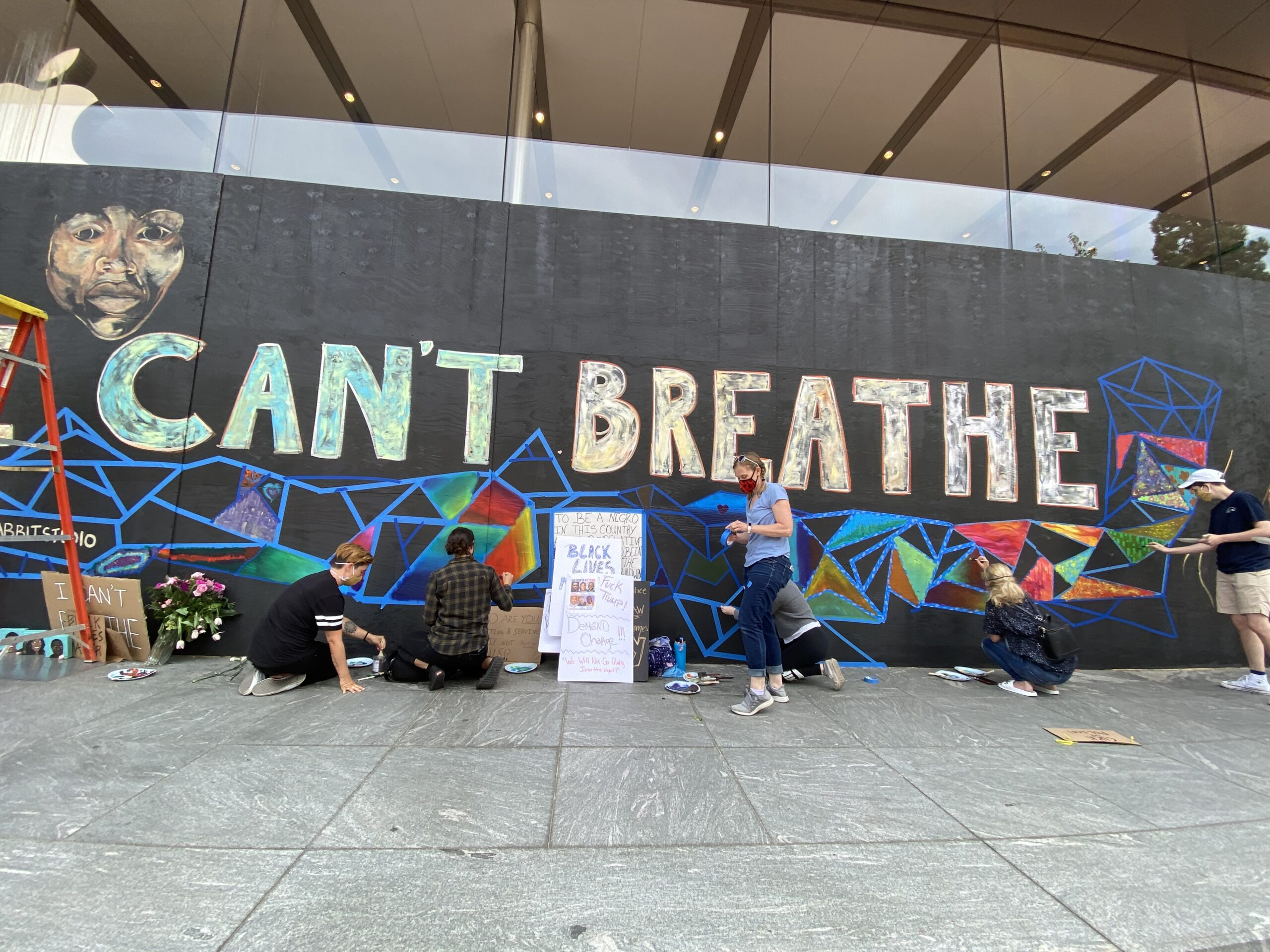 Photo of volunteers helping paint a mural on the downtown Portland Apple Store.